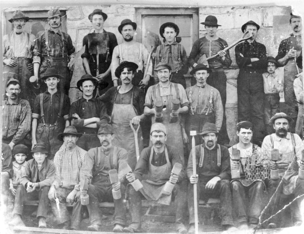 Men working as molders in Sharon Valley. Note the unusual variety of tools used for the compacting of special sand for casting the iron. Note: the children are not just visiting they are part of the work force. - Sharon Historical Society