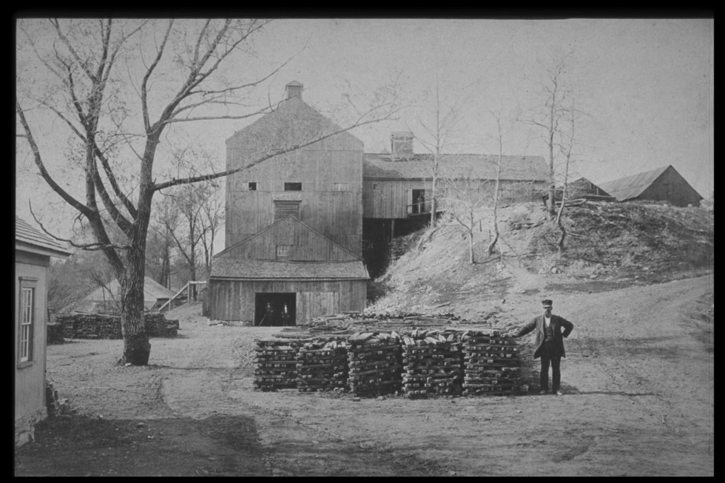 The Sharon Valley Iron Company furnace in 1875. Note the stacks of pig iron in the foreground and beyond the tree to the left. To the upper right stand the charcoal sheds. At the same level is the elongated casting shed running into the main building to the top of the thirty-four-foot-high blast furnace.  Above the unseen furnace is the top house extending sixty-eight feet above ground.  To the far left is the blast house with an overshot waterwheel powering pumping tubs through the visible pipe to the top house to heat the blast. The casting shed, center front, contains the sand beds where the white-hot iron formed into pigs and cooled. - Salisbury Association