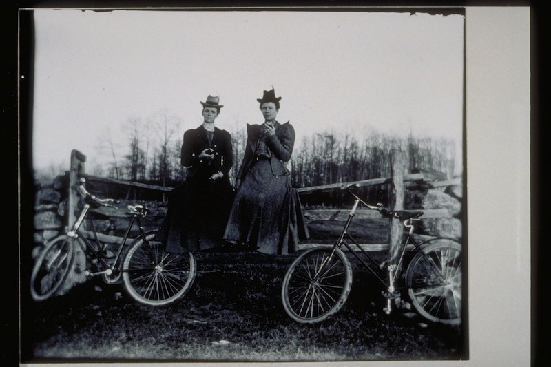 Two women sit on a split rail fence, ca. 1890-1899. Photograph by Edward H. Newbury - Mystic Seaport