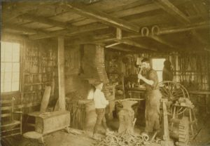 Man and boy in a blacksmith shop